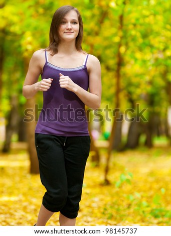 Young woman running outdoors on a lovely sunny winter (fall) day