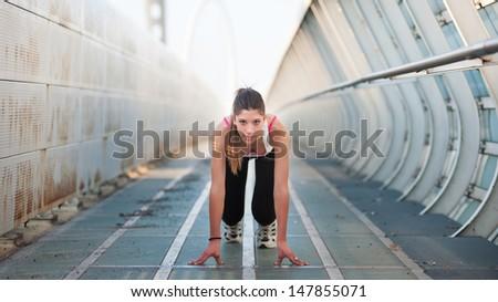 Young woman running outdoors on a modern bridge.