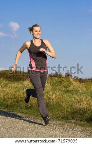 young woman runs  outdoor in a park