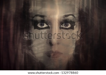 Young woman's face with gothic makeup through the transparent thin fabric