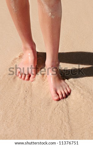 Young woman's feet on a sandy beach