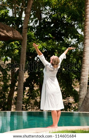 Young woman's figure with arms outstretched while standing at the edge of a swimming pool in a tropical nature location.