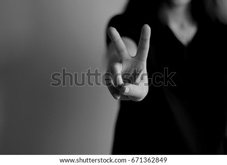 Young woman's hand shows V sign. Gesture #671362849