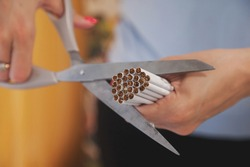 Young woman's hands cut cigarettes with scissors. Quit Smok, fight nicotine addiction addicts. Close-up of scissor cutting lot of cigarette. Concept of anti-Smoking and healthy lifestyle. Copy space