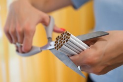 Young woman's hands cut cigarettes with scissors. Quit Smoking, fight nicotine addicts. Close up of scissors cutting lot of cigarettes. Concept of anti-Smoking