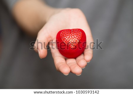 young woman's hands holding a red heart-shaped box #1030593142