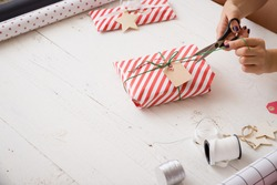 Young woman's hands wrapping Christmas gift in striped paper and decorating it with and twine and tag on white wooden background. Girl wrapping presents for the party.