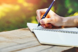 young woman's hands writing notes on notebook with pen on wooden table outdoor