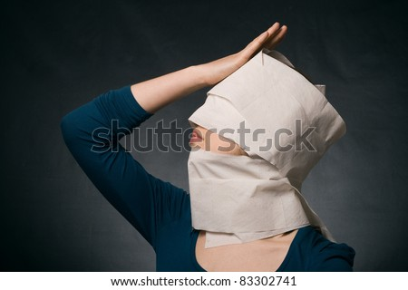 Young woman\'s head wrapped in paper. Symbol of loneliness and alienation.