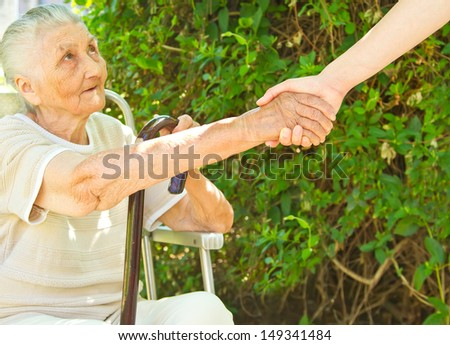 young woman\'s helping hand towards a very old woman sitting in the park