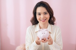 young woman 20s in casual clothing holding piggybank with lots of money isolated over pink background