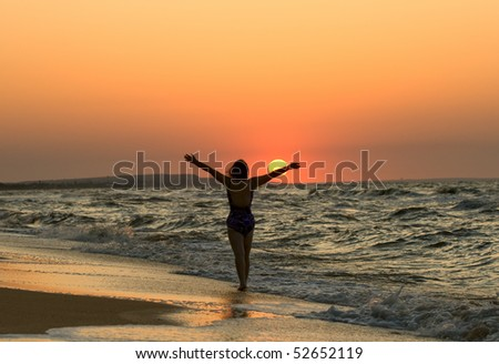 Young woman's silhouette in a sunset on a sea coast