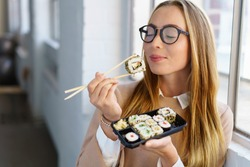 Young woman savoring her sushi lunch standing in front of a window in the office with her eyes closed and an expression of bliss as she anticipates the next mouthful