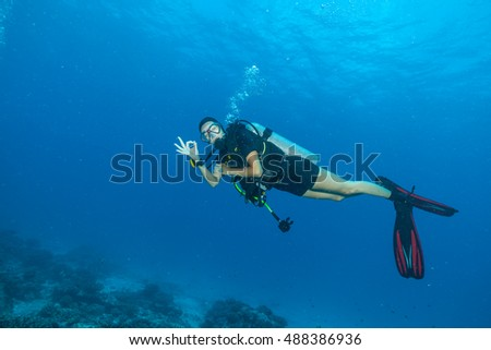 Young woman scuba diver exploring sea bottom. Showing ok sign. Underwater life with beautiful rocks and coral #488386936