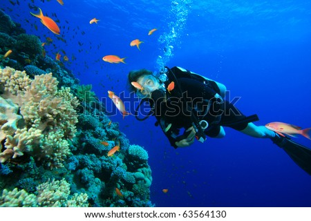 Young woman scuba diving on a beautiful coral reef