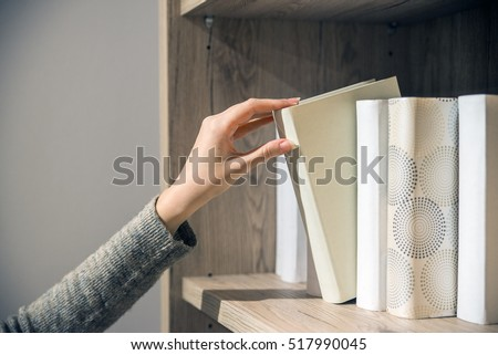 young woman searching for a book in bookstore. student selecting bookshelf library. female college student taking book from shelf in library. pretty young college student in a library