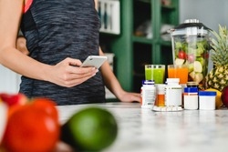 Young woman searching info about food supplements on her phone with fruits and additives on the table