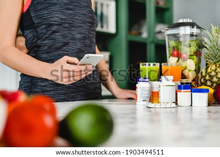 Young woman searching info about food supplements on her phone with fruits and additives on the table ストックフォト ©