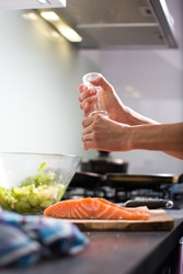Young woman seasoning a salmon filet in her modern kitchen, preaparing a healthy food