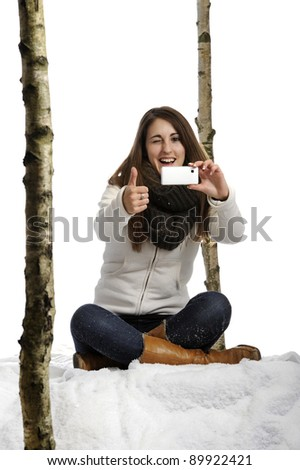 young woman seated in the snow taking a picture
