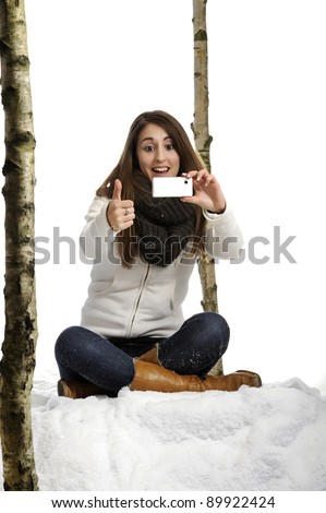 young woman seated in the snow taking a picture with her phone