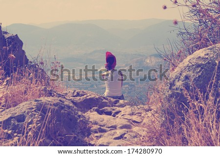 Young woman seating in the mountain. Greece. Vintage photo