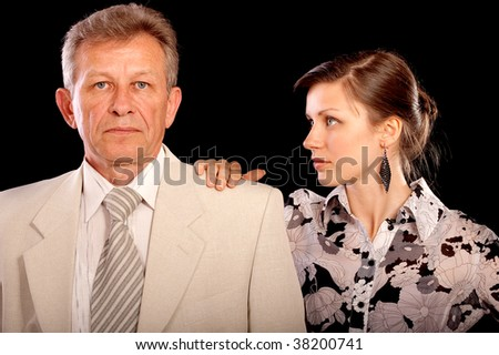 Young woman-secretary has put hand on shoulder of boss, it is isolated on black background.