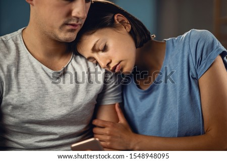 Young woman seeking for solace on boyfriend's shoulder while feeling sad about something.