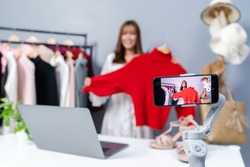 young woman selling clothes online by smartphone live streaming, business online e-commerce at home