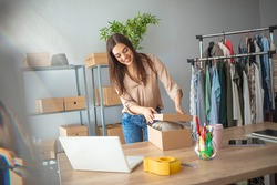 Young woman selling products online and packaging goods for shipping. Women, owener of small business packing product in boxes, preparing it for delivery