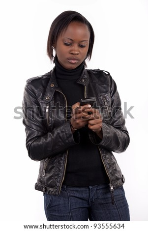 Young woman sending a text message from her cell phone.