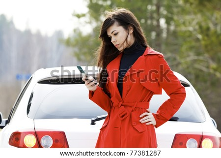 Young woman sending an sms to the car service.
