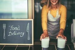 Young woman serving healthy take away food inside restaurant - Happy girl working inside delivery food ghost kitchen - Online business order service concept - Focus on hands
