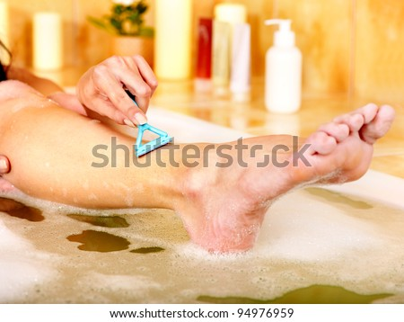 Young woman shaving her legs in  bath.