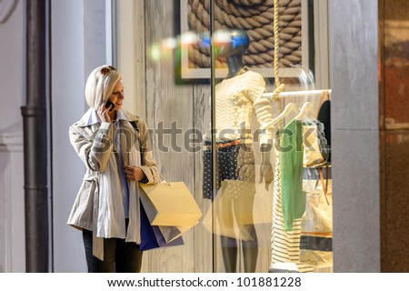Young woman shopping evening city looking into shop windows phone