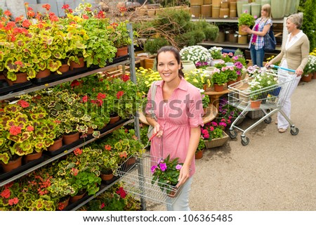 Young woman shopping flowers at garden center green house