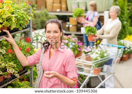 Young woman shopping flowers at garden centre green house