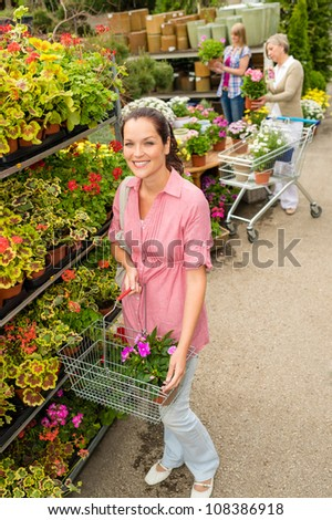 Young woman shopping flowers at market garden centre
