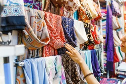 Young Woman Shopping For A New Scarf and choosing colorful fabric in bazar