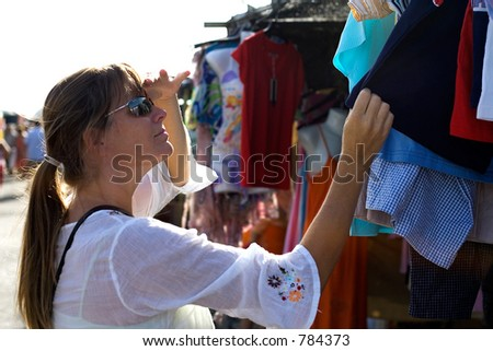 Young woman shopping for clothes at a Sunday market on the Costa del Sol in Spain