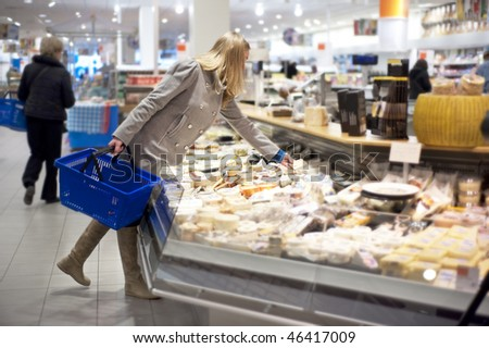 young woman shopping for groceries, and picking a piece of cheese from a display counter in a supermarket. Shallow depth of field - stock photo