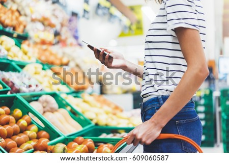Shutterstock Young woman shopping healthy food in supermarket blur background. Female hands buy nature products using smart phone in store. Hipster at grocery using mobile. Person comparing price of produce