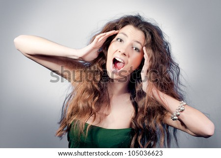 young woman shout and scream holding her hands on her head