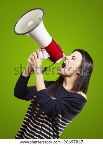 young woman shouting with a megaphone against a green background