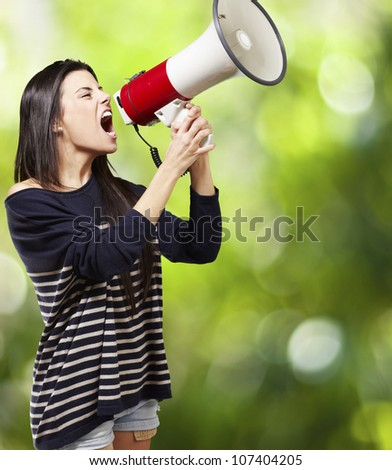young woman shouting with a megaphone against a nature background
