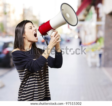 young woman shouting with a megaphone against a street background