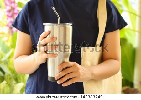 Young woman show reusable glasses of water in her hand with green garden background.Use water-glass and steel straw for Replacement plastic cup can save the earth.Reduce global warming concept. Foto stock ©