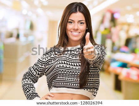 Young Woman Showing Best Of Luck Sign at a mall - stock photo
