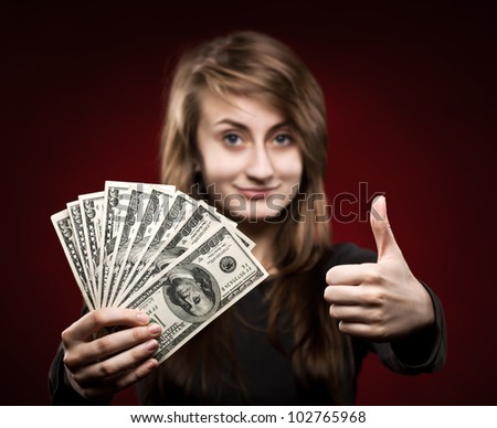 Young woman showing fan of money and sign OK with fingers