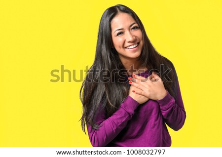 Young woman showing her heartfelt gratitude and thanks clasping her hands to her heart with a pleased smile on, Before Candy Background